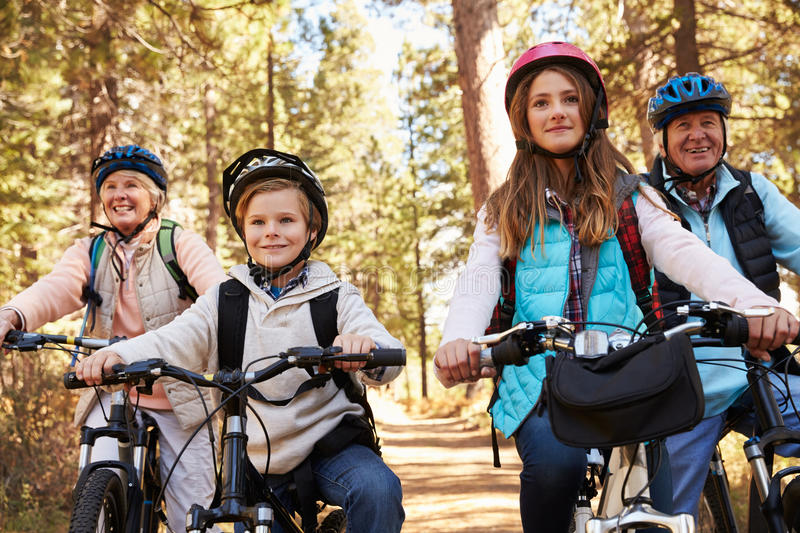 Grandparents and grandkids cycling on forest trail, close up royalty free stock images