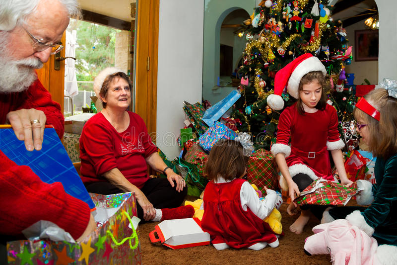 Grandparents and Grandkids Unwrap Christmas Presents royalty free stock images