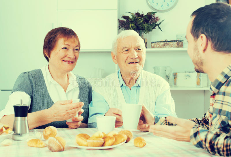 Grandparents and grandson breakfast. Elderly grandparents having breakfast with grandson sitting at table royalty free stock photo