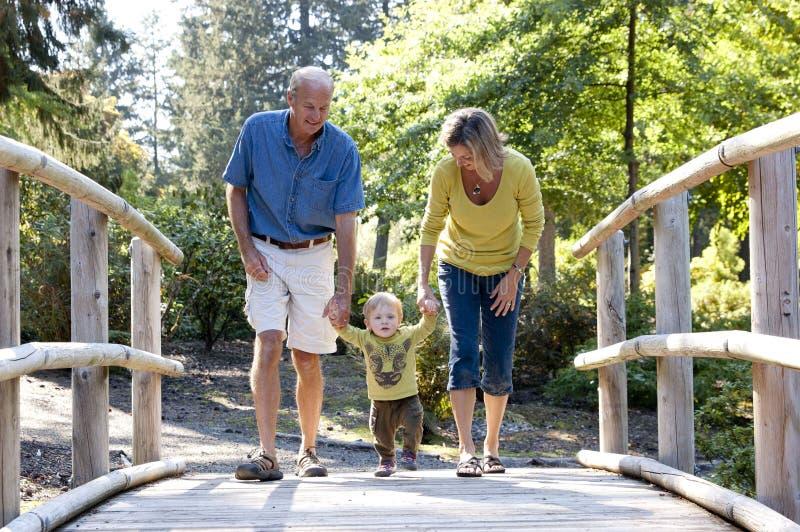 Grandparents and grandson walking on a bridge stock photo
