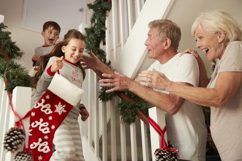 Grandparents Greeting Excited Grandchildren Wearing Pajamas Running Down Stairs Holding Stockings On Christmas Morning stock photos
