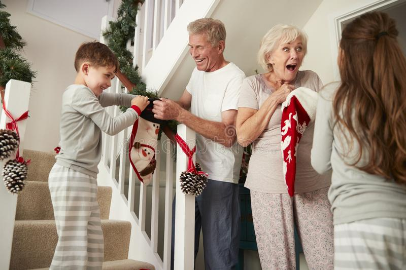 Grandparents Greeting Excited Grandchildren Wearing Pajamas Running Down Stairs Holding Stockings On Christmas Morning stock images