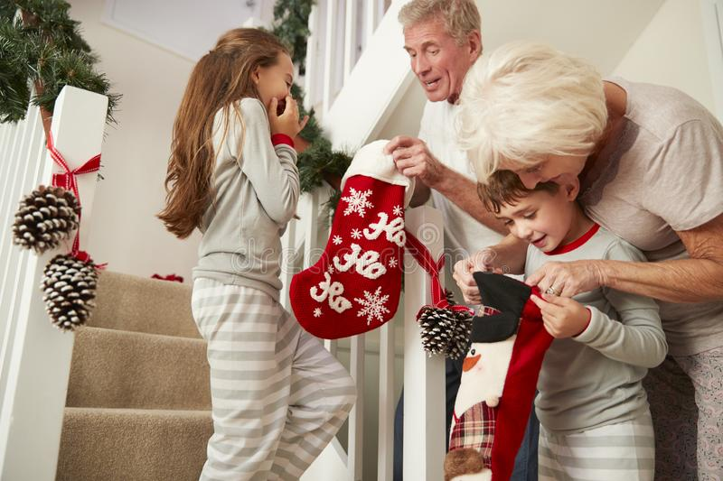 Grandparents Greeting Excited Grandchildren Wearing Pajamas Running Down Stairs Holding Stockings On Christmas Morning stock photography