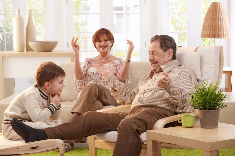Grandparents at home. Grandparents with grandson sitting in living room at home having fun together royalty free stock images