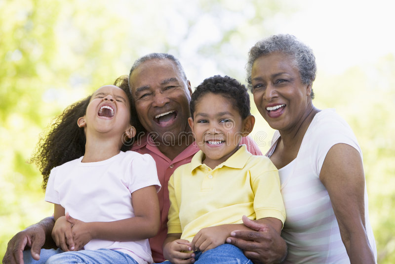 Grandparents laughing with grandchildren stock photo