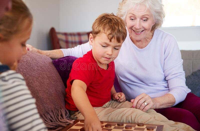Grandparents Playing Board Game Of Draughts With Grandchildren At Home royalty free stock photography