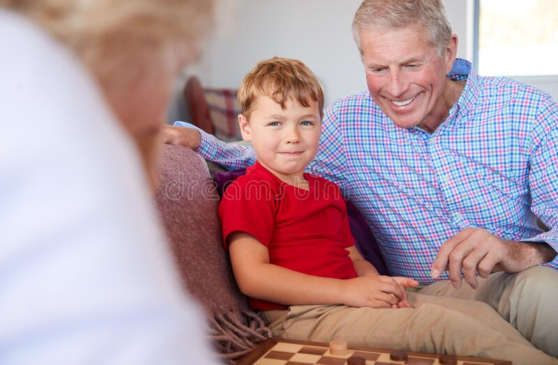 Grandparents Playing Board Game Of Draughts With Grandchildren At Home stock photos