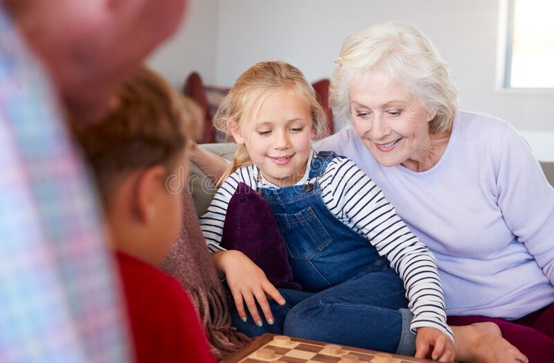 Grandparents Playing Board Game Of Draughts With Grandchildren At Home royalty free stock image