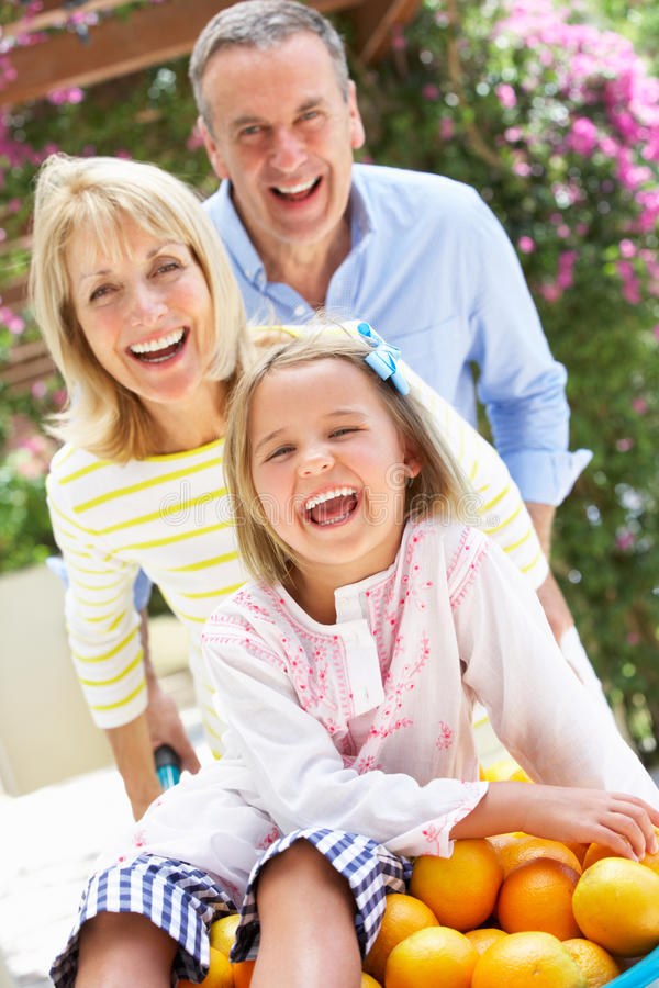 Grandparents Pushing Granddaughter In Wheelbarrow Royalty Free Stock Photography
