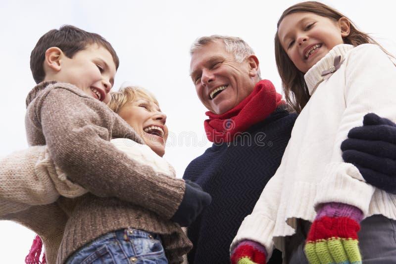 Grandparents que abraçam seus netos fotografia de stock royalty free
