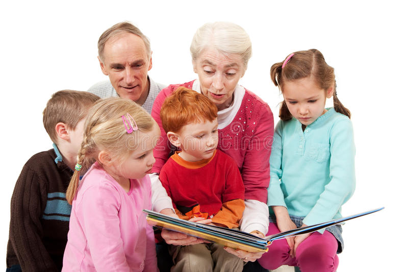 Grandparents que lêem o livro da história dos miúdos às crianças imagem de stock