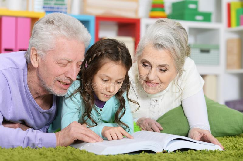 Grandparents reading book with little granddaughter. At home royalty free stock photos