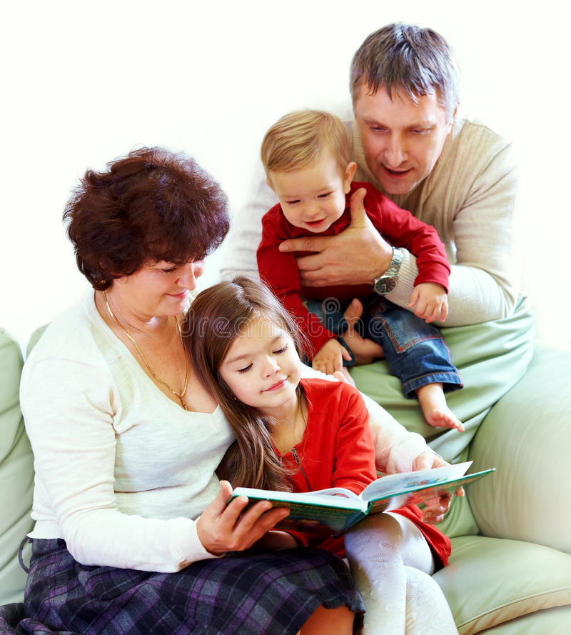 Grandparents reading books to grandchildren stock photo