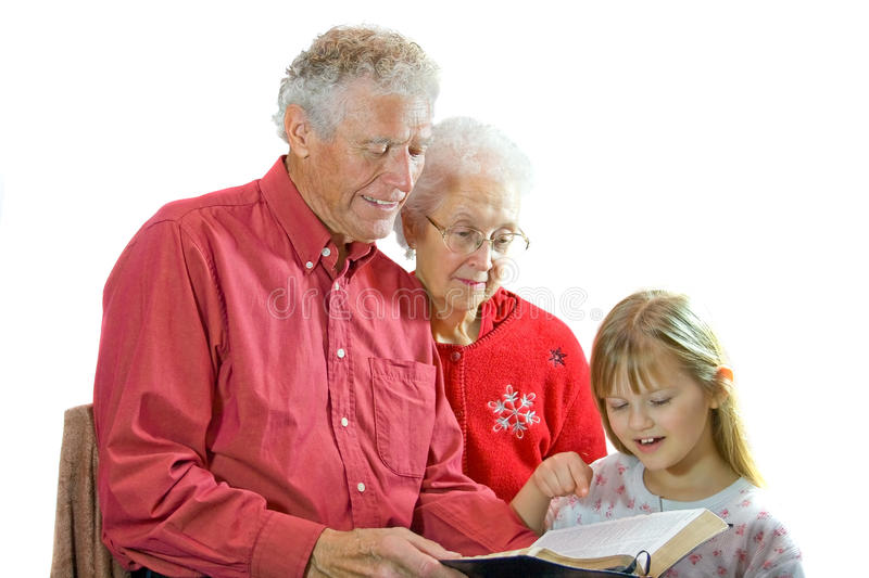 Grandparents reading to grandchild. royalty free stock image