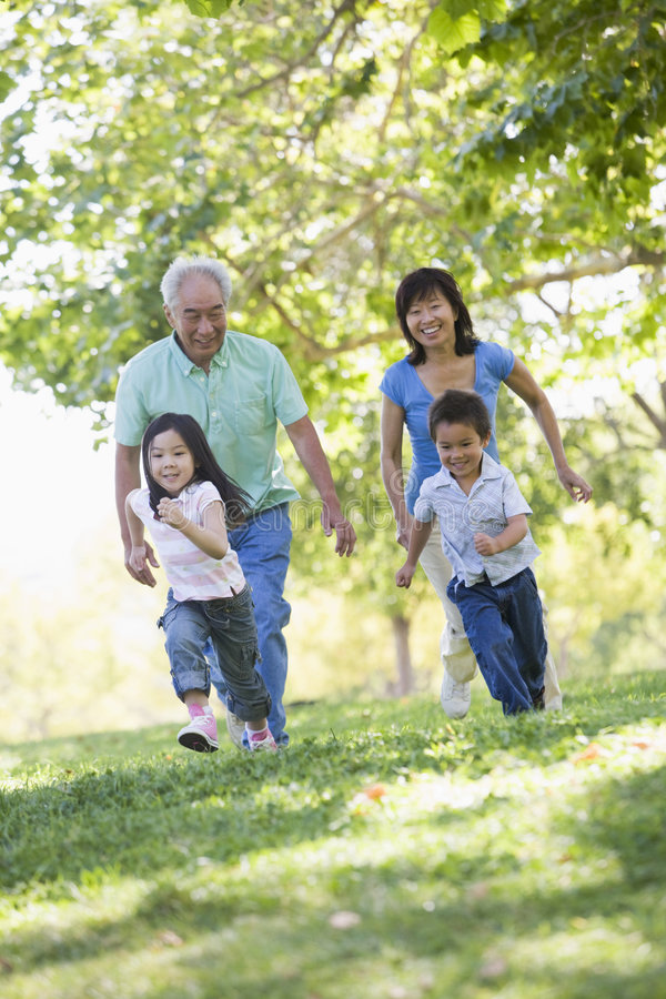 Grandparents running with grandchildren stock image