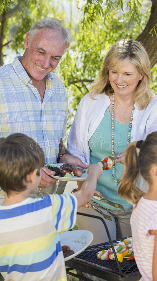 Grandparents Serving Grandchildren At Family Barbeque royalty free stock image