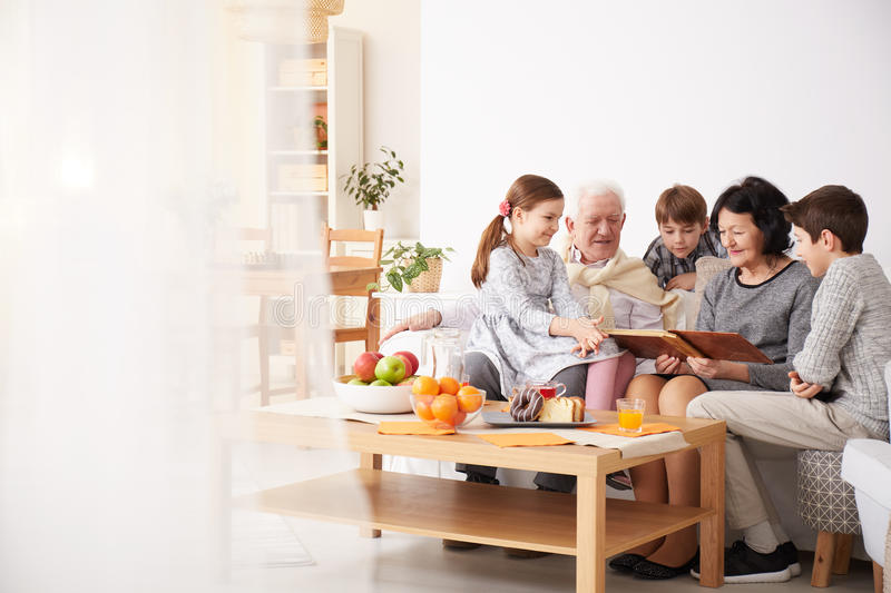 Grandparents showing photo album to their grandchildren. Happy grandparents showing photo album to their grandchildren in a living room royalty free stock photography