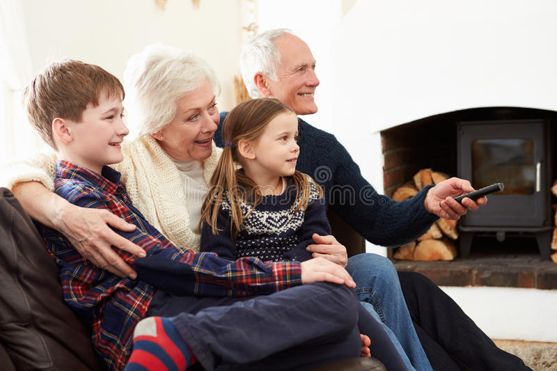Grandparents Sitting On Sofa Watching TV With Grandchildren royalty free stock photo