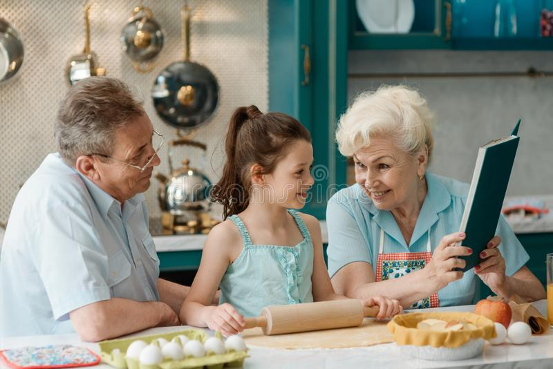 Grandparents teach granddaughter to bake stock images