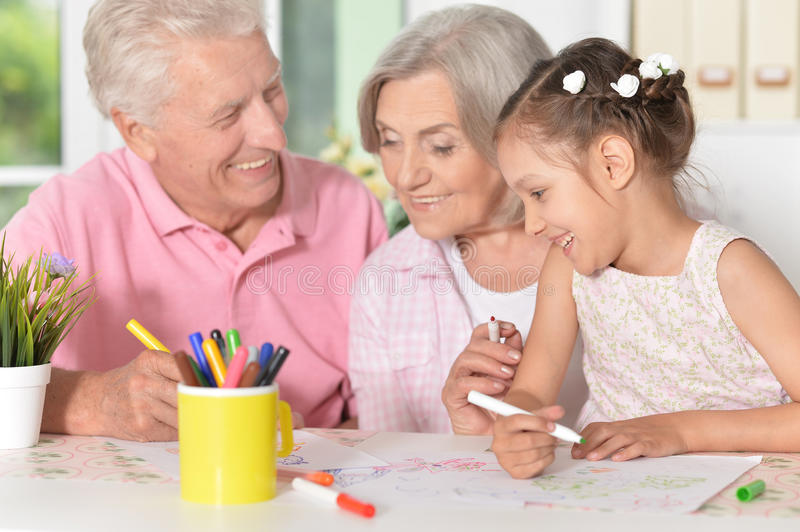 Grandparents with their granddaughter. Portrait of a grandparents with their granddaughter drawing together stock photography