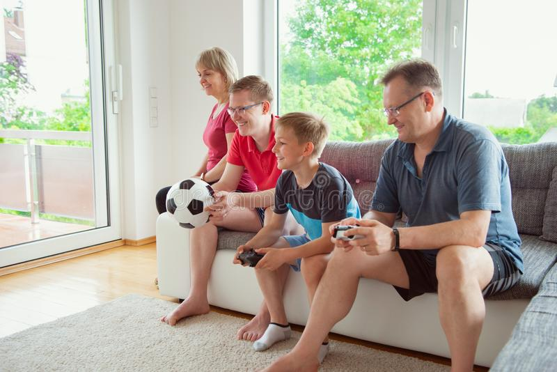Grandparents, their son and grandson are playing computer game royalty free stock image
