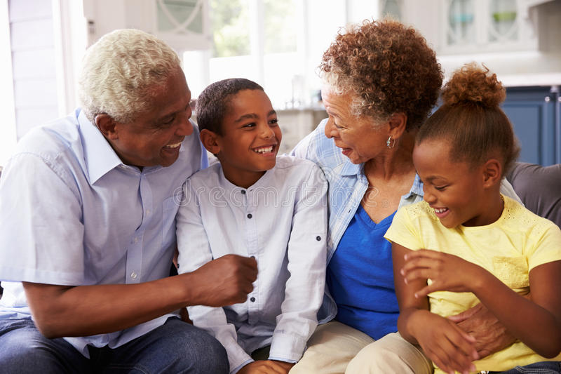 Grandparents and their young grandchildren relaxing at home royalty free stock image