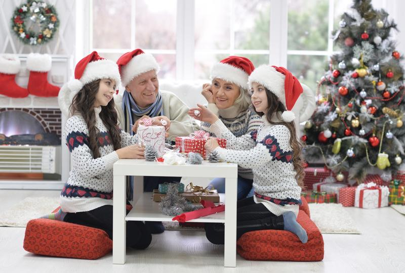 Grandparents with twin girls preparing for Christmas stock image
