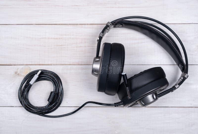 Grands écouteurs noirs pour des jeux de musique et d'ordinateur avec le microphone et le câble d'usb sur le fond blanc photographie stock libre de droits