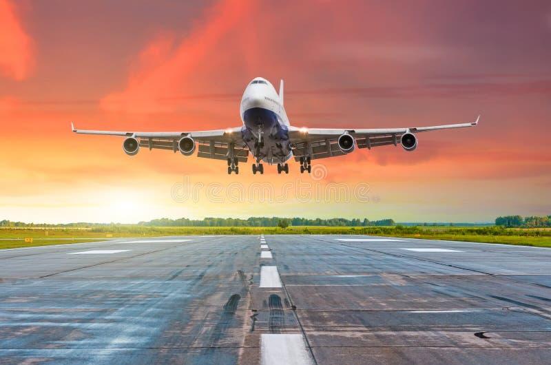 Grands avions longs-courriers avec quatre moteurs pilotant l'atterrissage d'arrivée sur une piste le soir pendant un coucher du s photographie stock libre de droits