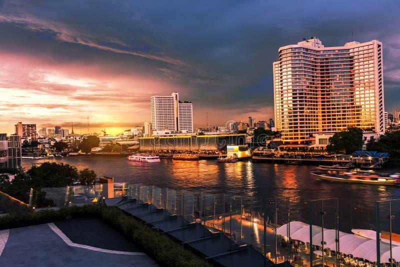 Grands bâtiments de la ville au bord de la rivière au coucher du soleil images stock