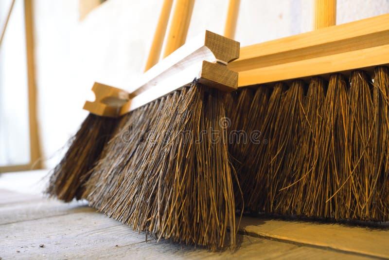 Grands balais sur les travaux domestiques en bois de plancher images libres de droits