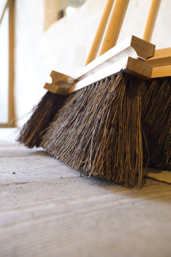 Grands balais sur les travaux domestiques en bois de plancher photo libre de droits