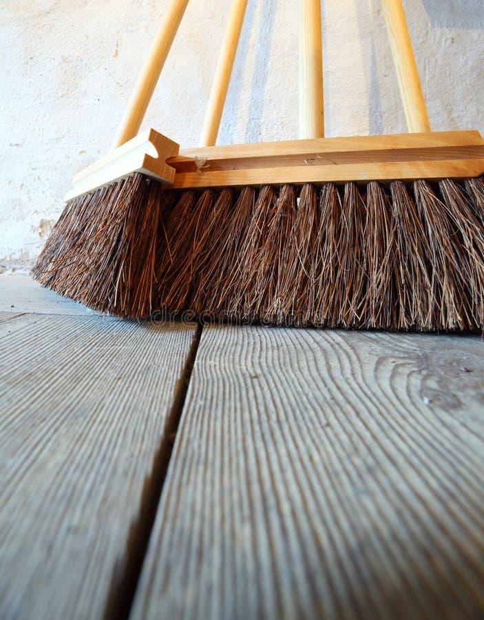 Grands balais sur les travaux domestiques en bois de plancher image libre de droits