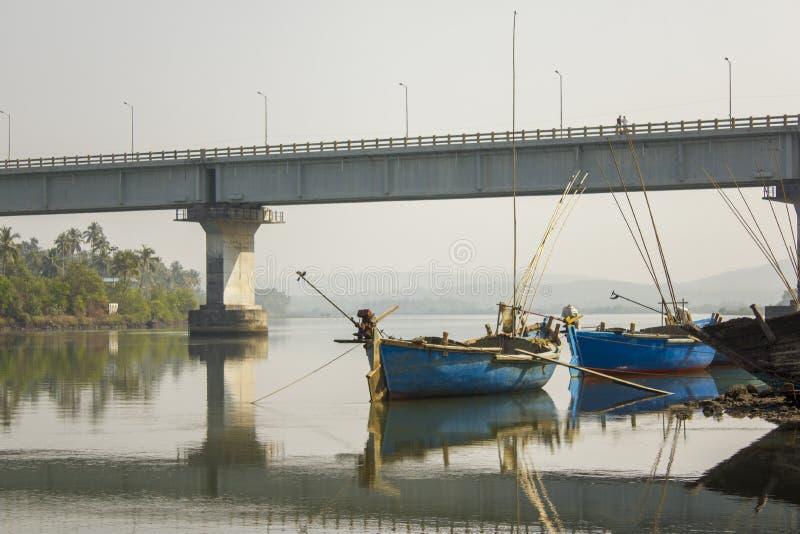 Grands bateaux de pêche vides et un pont au-dessus de la rivière et sa réflexion dans l'eau contre les arbres verts sur le rivage images stock