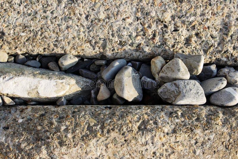 Grands blocs rectangulaires concrets pour protéger le rivage contre l'érosion Clôture des voies ferrées Entre les blocs photos libres de droits