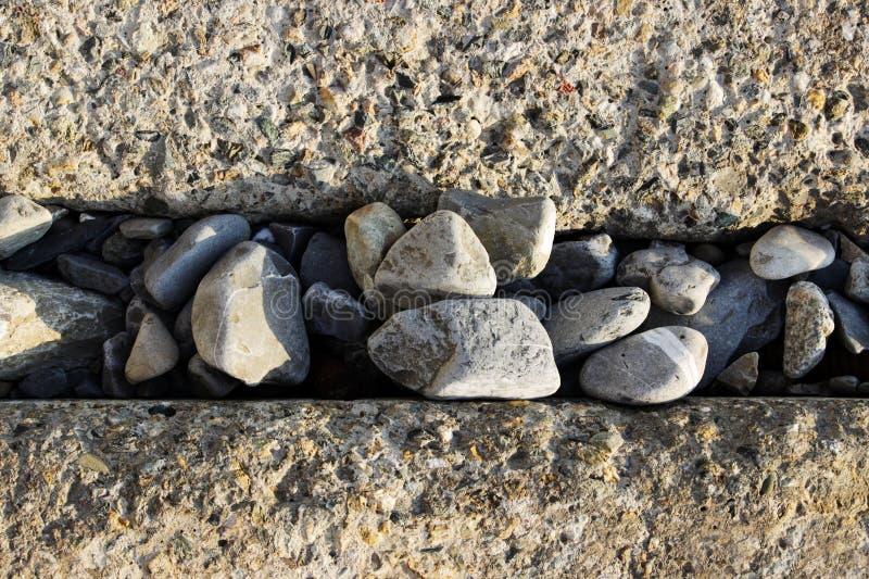Grands blocs rectangulaires concrets pour protéger le rivage contre l'érosion Clôture des voies ferrées Entre les blocs photographie stock libre de droits