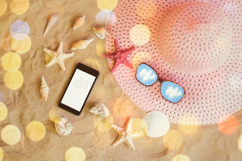 Grands chapeau, lunettes de soleil, smartphone, étoiles de mer et coquillages roses d'été sur la plage de sable image stock