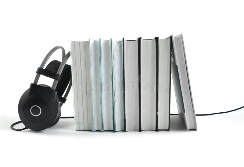 Grands ?couteurs noirs pr?s de la pile de livres sur le fond blanc Concept audio de livre Copiez l'espace image stock