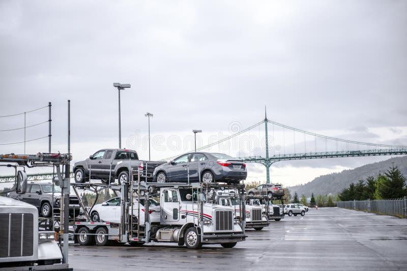 Grands d'installations de voiture de transporteurs camions semi avec les voitures chargées se tenant dans la rangée sur le parkin photos libres de droits