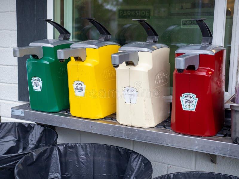 Grands distributeurs commerciaux de ketchup de Heinz, de moutarde, de goût, et d'extérieur de mayonnaise pour les hot-dogs et les images libres de droits
