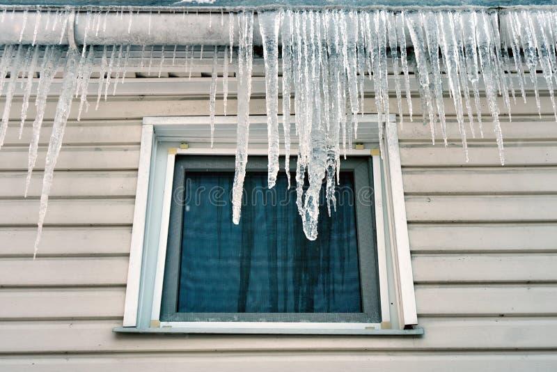 Grands glaçons accrochant sur le toit au-dessus d'une fenêtre d'un cottage en hiver ou printemps photographie stock