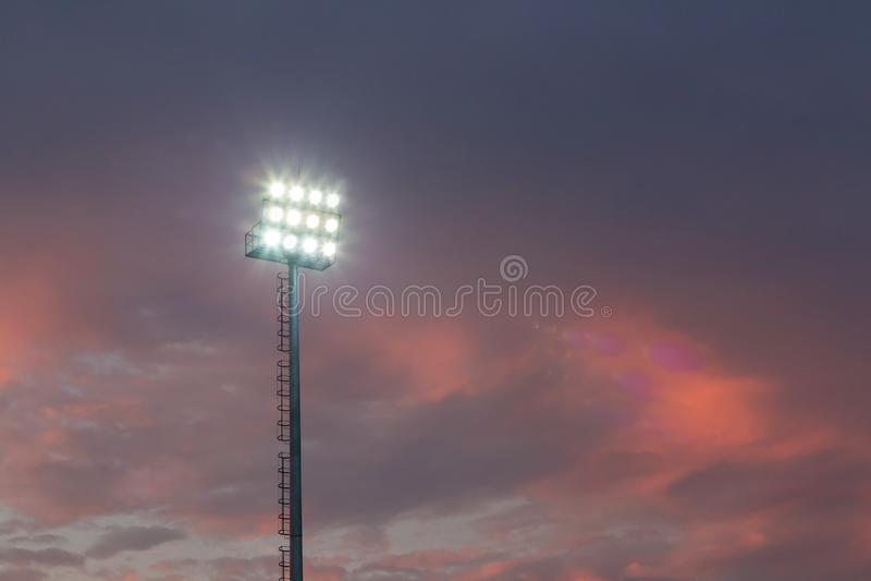 Grands hauts projecteurs extérieurs grands de stade sur la construction rigide de cadre sous la lumière du soleil naturelle photo stock