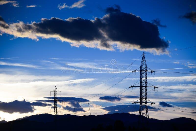 Grands nuages noirs au-dessus salut de la ligne de grille d'alimentation de tension photographie stock
