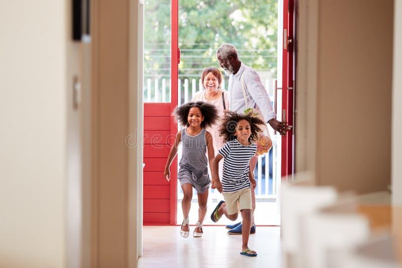 Grands-parents avec des petits-enfants retournant à la maison des sacs d'épicerie de transport de voyage d'achats photo libre de droits