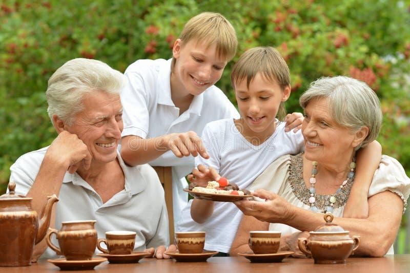 Grands-parents avec la consommation de petits-fils photographie stock libre de droits