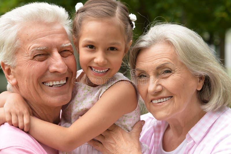 Grands-parents avec la petite-fille en parc photo stock