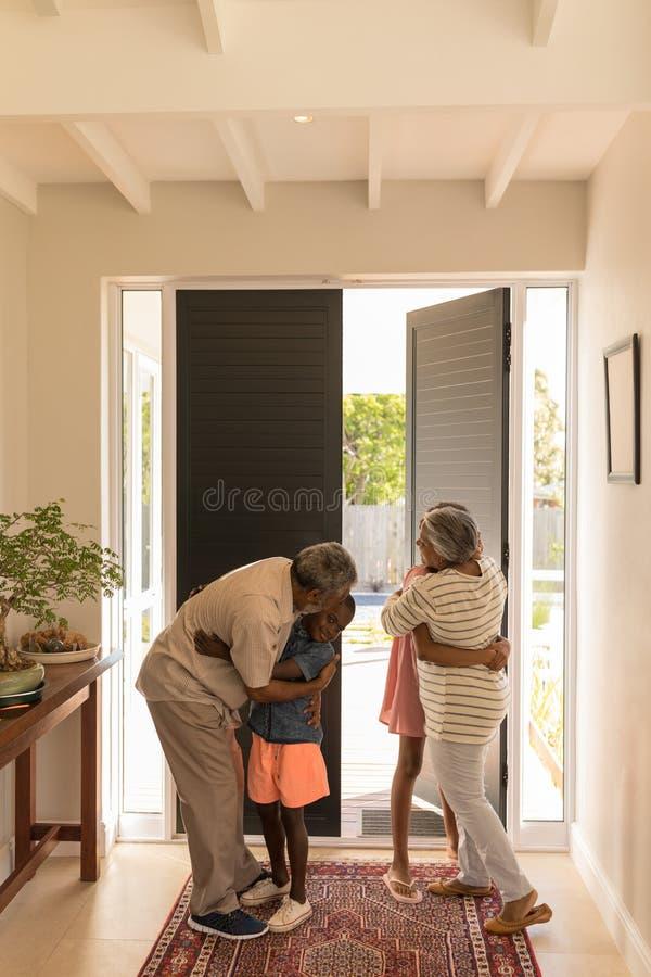 Grands-parents caressant leurs petits-enfants à la maison image stock