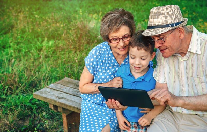 Grands-parents et petit-fils à l'aide du comprimé se reposant sur un banc photos libres de droits