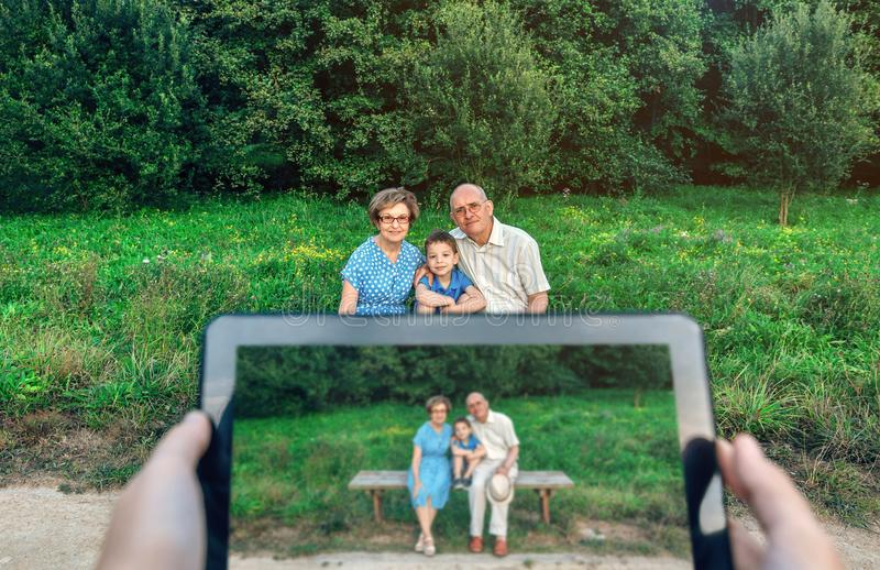 Grands-parents et petit-fils posant pour une photo avec le comprimé images stock