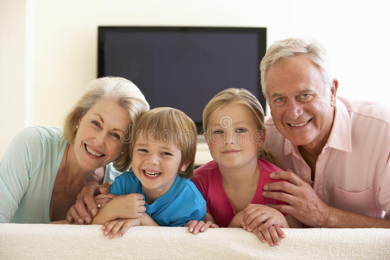 Grands-parents et petits-enfants observant l'écran géant TV à la maison photo libre de droits